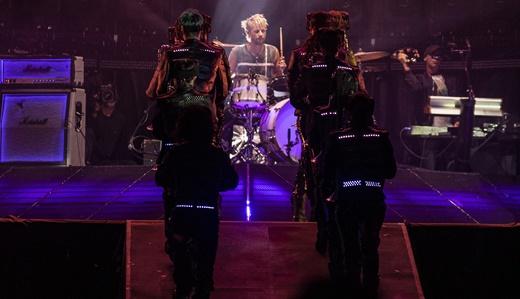 Futuro ou passado? No fundo do palco o baterista Dominic Howard recebe a tropa de robôs