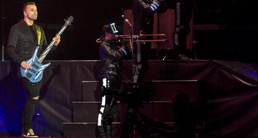 O baixista Chris Wolstenholme toca ao lado da tropa de robôs, que usam instrumentos de sopro