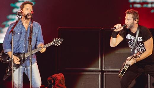 O guitarrista Ryan Peake toca ao lado de Kroeger em um dos shows mais concorridos do domingo