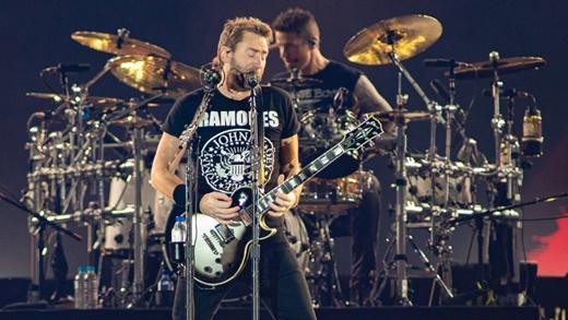 Chad Kroeger com camiseta do Ramones e a guitarra em punho; atrás, o baterista Daniel Adair