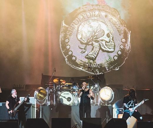 Sepultura tocando e a imagem que dever ser a da capa do novo álbum, 'Quadra', é exibida nos telões
