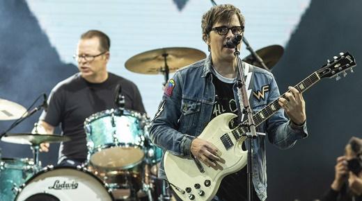 O líder do Weezer toca e canta com olhar desconfiado, com o baterista Patrick Wilson no fundo